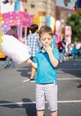 image of candy cotton  - Portrait of cute child eating cotton candy over a summer fair festival background - JPG