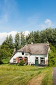 picture of neglect  - Abandoned and neglected historic farmhouse down a Dutch embankment. ** Note: Soft Focus at 100%, best at smaller sizes - JPG