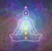 foto of chakra  - Silhouette of man sitting in lotus position meditating in energy matrix with seven chakras displayed in their accepted positions - JPG
