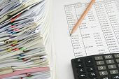 stock photo of accountability  - Stack document of account include sales and receipt on finance account with pencil and black calculator - JPG