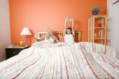 pic of shelving unit  - Young couple stretch their arms as they wake up from a striped bed - JPG