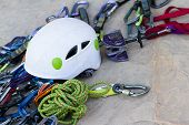 image of climb up  - close up of technical rock climbing gear layer out on a rock - JPG