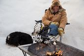 stock photo of sherpa  - A man and his dog huddles by a fire toasting a marshmallow on a stick while fully surrounded by snow - JPG