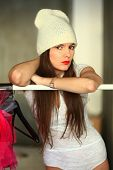 stock photo of knitted cap  - the girl in a white knitted cap with red lipstick on lips costs near a hanger for clothes