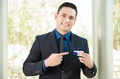 stock photo of rep  - Young Latin man wearing a suit and holding and pointing at a credit card - JPG
