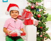 foto of ball cap  - Happy little boy in Christmas cap with presents and big smile sitting on the sofa near New year tree wearing Santa Claus cap - JPG