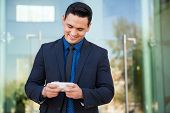 pic of laws-of-attraction  - Happy young businessman using a smart phone to update his social media status at work - JPG