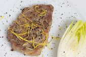 pic of chicory  - Slice of juicy pork chop and chicory on white plate. ** Note: Soft Focus at 100%, best at smaller sizes - JPG