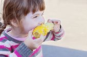 image of sweet-corn  - Beautiful little girl eats boiled sweet corn outdoor at summer - JPG