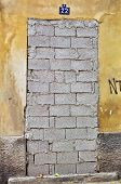 stock photo of oddities  - Bricked up door and weathered wall of an abandoned building - JPG