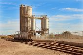 picture of caboose  - Stationary cargo train wagons next to Mill and Silo along train tracks in desert outside of Phoenix - JPG