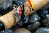 picture of fly rod  - Close up of trout flies focus on front one with shallow depth of field on wet cork handle of fishing rod with blurred out river rocks in background  - JPG
