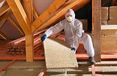 image of thermal  - Man laying thermal insulation layer under the roof  - JPG