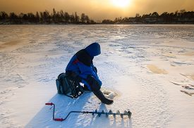 stock photo of ice fishing  - Ice fishing on thick ice with hand ice auger in front - JPG