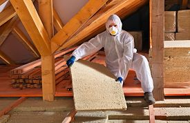 picture of thermal  - Man laying thermal insulation layer under the roof  - JPG