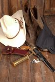 pic of pistols  - A cowboy hat black powder pistol and boots on a wooden background - JPG