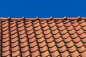 stock photo of roof tile  - Red roof tile pattern over blue sky - JPG