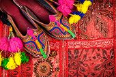 image of flea  - Colorful ethnic shoes and camel decorations on red Rajasthan cushion cover on flea market in India - JPG