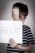 pic of scared  - Scared and abused young boy holding the paper with handwritten help sign - JPG