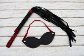 stock photo of flogger  - BDSM Toy A black and red BDSM toy a whip and mask over a distressed wood background - JPG