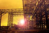 stock photo of sun flare  - metal structure of industry chemical tube in heavy industrial estate against beautiful sun rising with lens flare effect use for industry background - JPG
