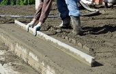 picture of concrete pouring  - Picture of a workers smooth concreting the floor - JPG