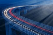 foto of moonlight  - Blurred lights of vehicles driving in night on a tall viaduct lit by moonlight with wind barriers long exposure - JPG