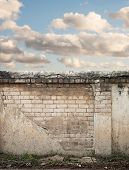 image of wall cloud  - Blue sky with clouds behind the cracked wall background - JPG