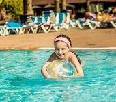 stock photo of pool ball  - cute little girl playing in the pool with colorful ball - JPG