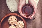 pic of crispy rice  - Woman wearing white woollen sweater holding cup of black teaand rice crispy balls in bowl on brown wooden background - JPG