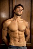pic of shirtless  - Sexy handsome young man standing shirtless in his bedroom against wooden wardrobe door - JPG