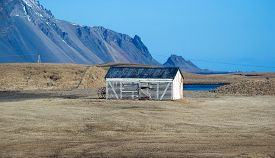stock photo of iceland farm  - A solitary farm house stands on the vast grass fields in a farm in Stokksness - JPG