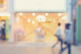 stock photo of department store  - Defocused shopping mall interior store front with women walking in pastel colors - JPG