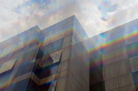 stock photo of prism  - Glass building windows facade motion blur through prism. Abstract spectrum colors reflection.