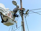 stock photo of katrina  - a electrical lineman repairing utility poles after hurricane katrina - JPG