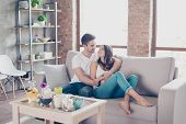 Cute Couple In Love In The Weekend Morning. They Are Hugging On The Sofa Indoors At Home, Wearing Ca poster