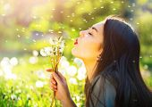 Beautiful Young Woman lying on the field in green grass and blowing dandelion. Outdoors. Enjoy Natur poster