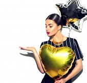 Beautiful fashion model party girl with colorful heart and star shaped balloons posing at studio iso poster