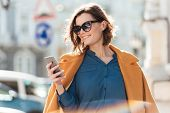 Smiling casual woman in sunglasses looking at mobile phone while standing on a city street poster