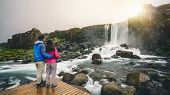 Couple Travelers Travel To Oxararfoss Waterfall In Thingvellir National Park, Iceland. Oxararfoss Wa poster