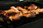 Chicken Drumsticks Left Cooking On Outdoor Barbeque poster
