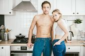 Two young people in love are posing in the kitchen. Love affair, jeans, interior. poster