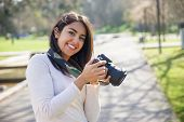 Positive Successful Photographer Enjoying Photo-shooting Outdoors. Young Woman In Casual Holding Pho poster