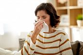 healthcare, cold, allergy and people concept - sick woman blowing her runny nose in paper tissue at  poster
