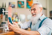 Hipster Man Using Mobile Phone While Sitting In A Bar - Senior Male Watching On New Trends Smartphon poster