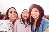 Happy Asian Girls Taking Selfie With Mobile Smartphone Outdoor - Young Social Friends Having Fun Tak poster