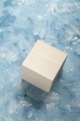 Bright wooden cube on white and blue painting surface. Wooden cube and a piece of fine art studio sh poster