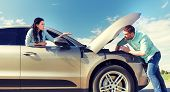 road trip, transport, travel and people concept - family couple with open hood of broken car at coun poster