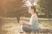 Side View.young Woman Meditating In Lotus Position Outdoors poster