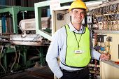 male caucasian industrial techincian portrait in front of machinery